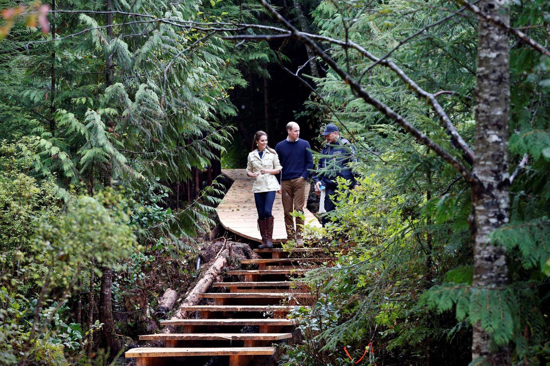 """Sie stehen und gehen im Wald - Kate und William besuchen den """"Great Bear Rainforest"""" in Bella Bella, British Columbia. Dieses Gebiet, der so genannte """"Amazonas des Nordens"""", gehört zu einem Commonwealth-weiten Naturschutzprojekt, """"Queen's Canopy Commonwealth initiative"""". 85 Prozent dieses Waldes sollen in Zukunft vor der industriellen Verwertung geschützt sein.   In einer Rede sagt William, dem das Thema Naturschutz sehr am Herzen liegt: """"Wenn wir unsere Flüsse, Ozeane, Atmophäre und Wälder schützen, signalisieren wir damit unseren Kindern auch, dass unser zukünftiges Wohlergehen nicht ohne eine gesunde, naturnahe Umgebung funktioniert.""""  Und mit Blick auf das Wetter, noch sehr viel pragmatischer: """"Wer in den Regenwald kommt, muss damit rechnen, nass zu werden."""""""
