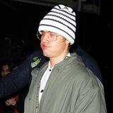 """Hot or Not? Justin Bieber mit fieser Grimasse, Bartflaum, Nerdbrille und Strickmütze beim Besuch der Afterparty der Premiere """"I Am Bolt"""" im Tape Club in London."""
