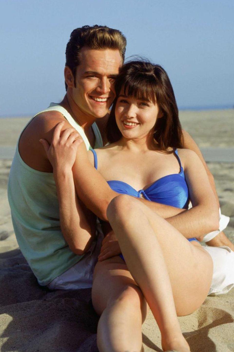"""Luke Perry und Shannen Doherty in der TV-Serie """"Beverly Hills 90210"""". Mit den Rollen """"Dylan McKay"""" und """"Brenda Walsh"""" wurden sie weltberühmt. Während der sichtbar gealterte Luke Perry heute weiterhin im TV-Business tätig ist, kämpft Shannen Dorherty gegen ihre Krebserkrankung."""