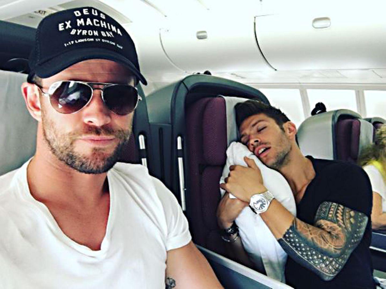 November 2016   Chris Hemsworth sitzt mit seinem Trainer Luke Zocchi im Flieger. Der hat sich in seinem Sitz eingekuschelt und schläft tief und fest, während sich Chris ironisch für die gute Unterhaltung bedankt.