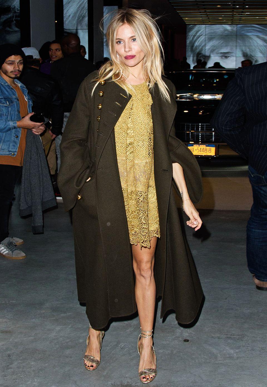 """Im goldgelben Spitzenkleid, über dem sie einen dunklen Lodenmantel trägt, strahlt Sienna Miller auf der """"Letters to Andy Warhol""""-Ausstellung in New York."""