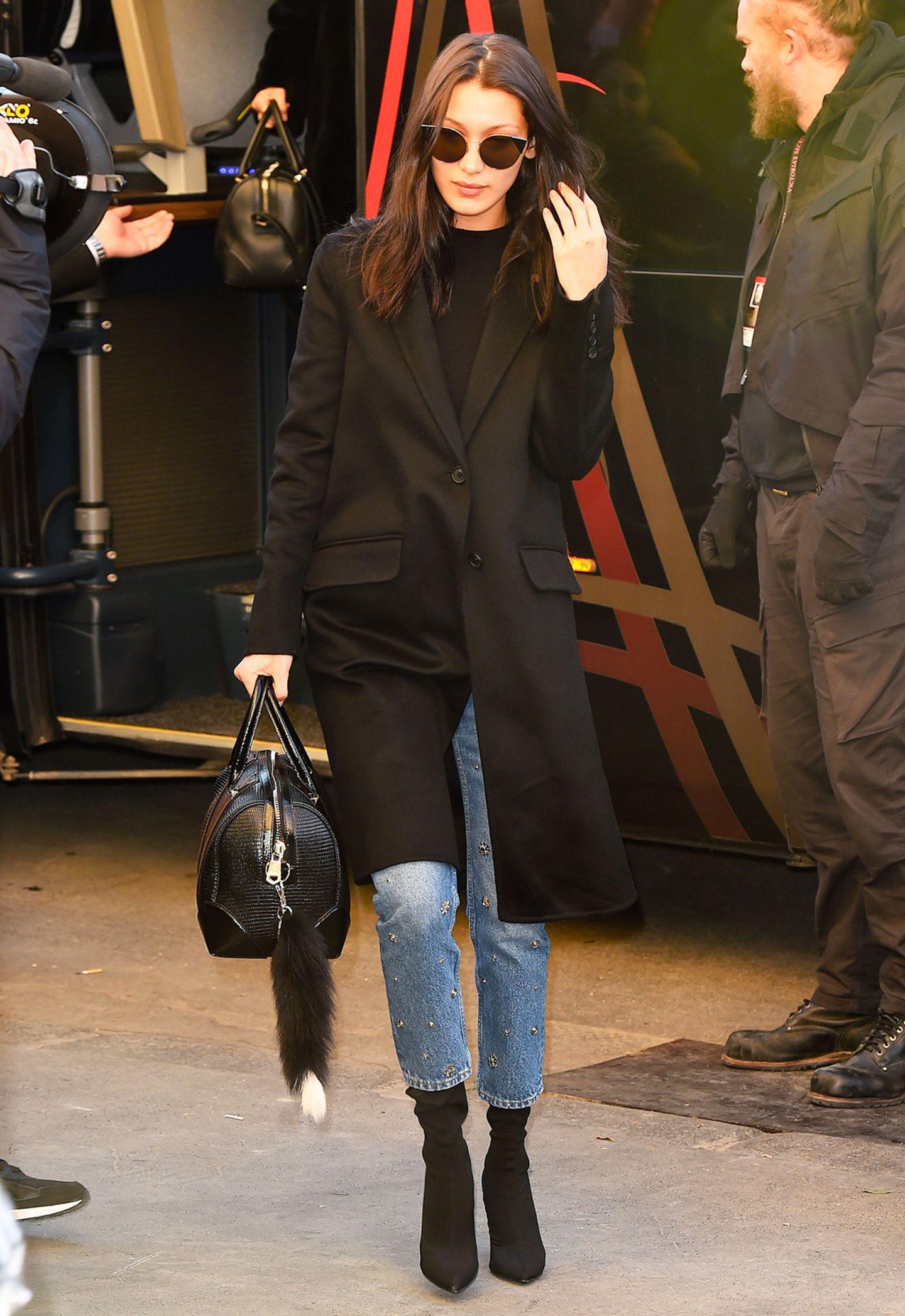 Bella Hadid kombiniert den edlen, schwarzen Mantel mit bestickter Jeans.