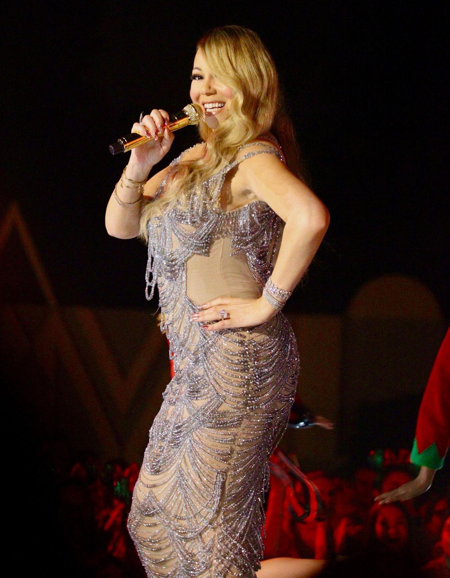 """Mariah Carey sang ihren Weihnachts-Song """"All I Want for Christmas Is You"""" in einem knallengen Schlauchkleid. Lilafarbene Glitzerpartien zieren das hautfarbene Stück und spiegeln sich auch in ihrem Schmuck wie dem Armband wieder. Einen Gefallen hat sich die Diva mit diesem viel zu eng anliegendem Dress wirklich nicht getan."""