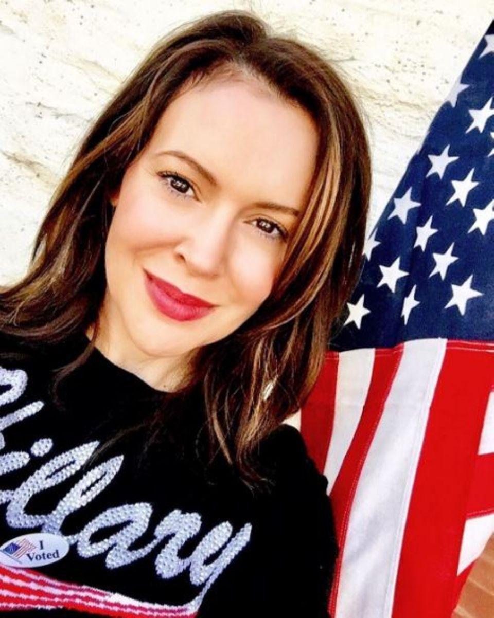 Alyssa Milano trägt einen Pulli mit Glitzer-Hillary-Schriftzug.
