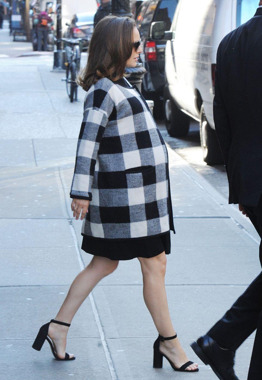 Einen Hauch von Audrey Hepburn versprüht die schwangere Natalie im großkarierten Wollmantel über dem schwarzen Kleid.