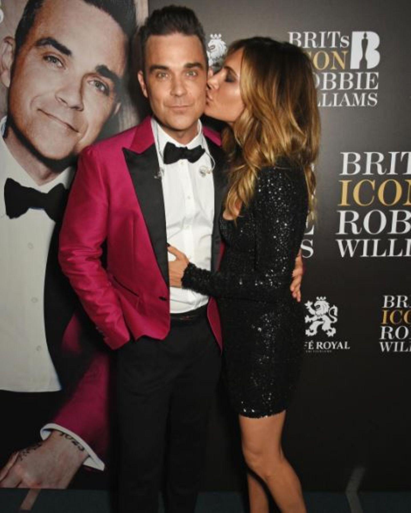 """November 2016   Das neue Album """"The Heavy Entertainment Show"""" hat eingeschlagen, es läuft sehr gut für Robbie Williams. Ayda Field überschüttet ihren Liebsten mit Komplimenten und kann es einfach nicht für sich behalten. Sie ist stolz auf ihren Robbie."""
