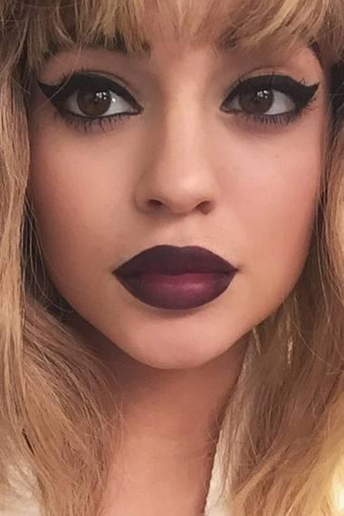 Kaum wiederzuerkennen ist Kylie Jenner mit blonder Perücke, extremem Eyeliner und dunklen Lippen.