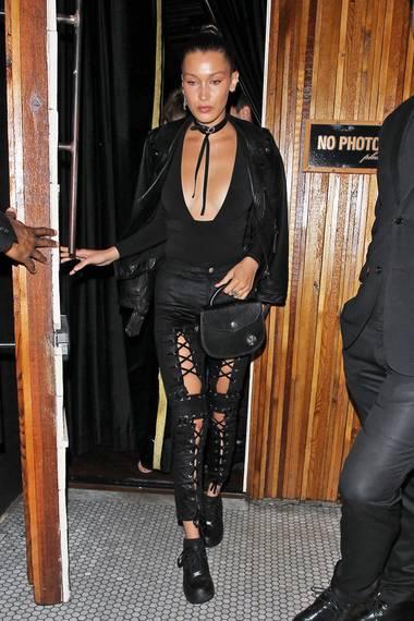 Bella Hadid bevorzugt beim Party-Styling eher die Rocker-Variante mit supertiefem Ausschnitt, Lederjacke und enger Hose mit Schnür-Details.