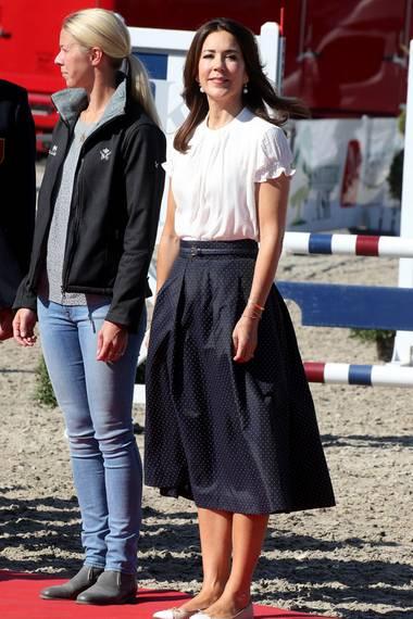 """Prinzessin Mary trägt bei den Europameisterschaften im Ponyreiten einen blauen Rock mt weißen Punkten vom dänischen Label """"Baum und Pferdgarten"""" und eine weiße kurzärmelige Bluse. Hingucker ist ein Taillengürtel, den sie zu dem Rock trägt."""
