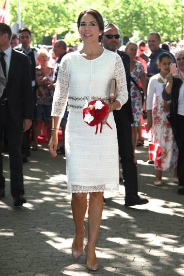 Zum 825. Jubiläum der dänischen Stadt Glostrup trägt Prinzessin Mary ein ganz ähnliches weißes Kleid. Passend dazu kombiniert sie - wie auch Victoria - weißen Haarschmuck aus einer Schleife und Federn.