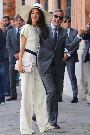 29. September 2014: Amal Clooney trägt in Venedig zur standesamtlichen Hochzeit mit George Clooney einen weißen Hosenanzug von Stella McCartney. Dazu einen großen Schlapphut. Hat Amal damit die Nase vorn im venezianischen Braut-Duell?