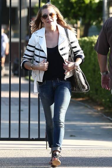 Auch die Sängerin trägt die weiße Lederjacke mit Slim-Jeans.