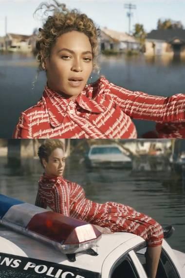 """Im offiziellen Video für ihren Song """"Formation"""" ist Beyoncé im rot-weißen Kleid des Luxuslabels Gucci auf dem Dach eines Polizeiwagens in den Flutmassen New Orleans' zu bewundern."""
