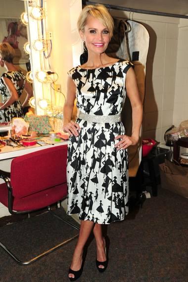 Kristin Chenoweth setzt auf Glamour und kombiniert das Cocktail-Kleid mit niedlichen 50er-Jahre-Fashion-Motiven vom Label Muse mit einem Strassstein-besetzten Gürtel.