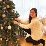 Oh Tannenbaum, oh Tannenbaum! Ana Ivanovic zeigt sich vorm festlich geschmückten Tannenbaum im Wohlfühl-Look. Der besteht aus einem weißen Pullover mit Zopfmuster, einer schwarzen Hose sowie Stiefeln mit stylischen Fransen.