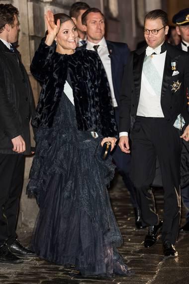 Unter der schwarzen (hoffentlich) Kunstfell-Jacke trägt Prinzessin Victoria für die Feierlichkeiten der schwedischen Akademie ein nachtblaues Spitzenkleid.