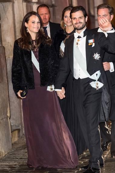 Prinzessin Sofia trägt zwar auch eine schwarze Felljacke, ihr pflaumenfarbenes Abendkleid darunter bringt aber im Vergleich zu Victoria und Madeleine zumindest ein klein wenig Farbe in die schwedische Akademie.