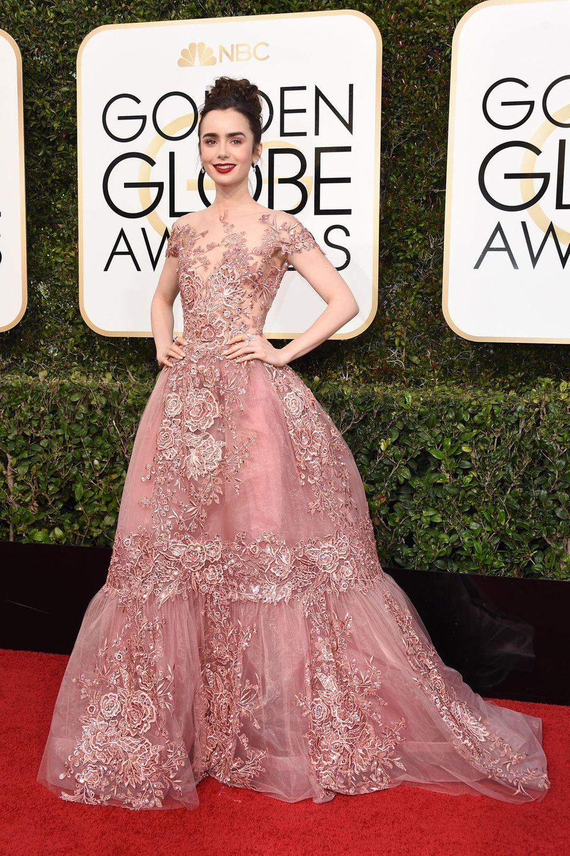 Wie eine Märchenprinzessin sieht Lily Collins in ihrer romantischen Robe von Zuhair Murad aus. Passend zum Altrosé des Kleides sind die Augen im gleichen Farbton geschminkt. Die locker hochgesteckten Haare machen den zarten Look perfekt.