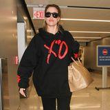 """Nanu, was für eine verrückte Zusammenstellung. Khloe Kardashian reist zwar im lässigen Gemütlich-Look mit Sweater und schmaler Hose, akzentuiert diesen jedoch mit einer sündhaft teuren """"Birkin Bag"""" aus Krokoleder, die schnell mal 40.000 Euro kosten kann."""