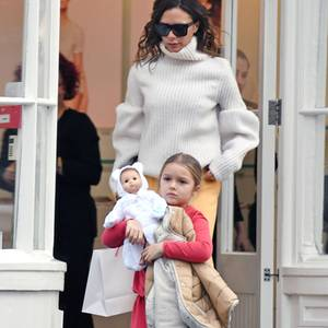 Stylisches Mutter-Tochter-Duo: Victoria Beckham und ihre Tochter Harper spazieren durch London. Victoria trägt zur gelben Schlaghose einen hellen Strickpulli. Harper ist in einem roten Kleidchen und grauer Wollstrumpfhose unterwegs.