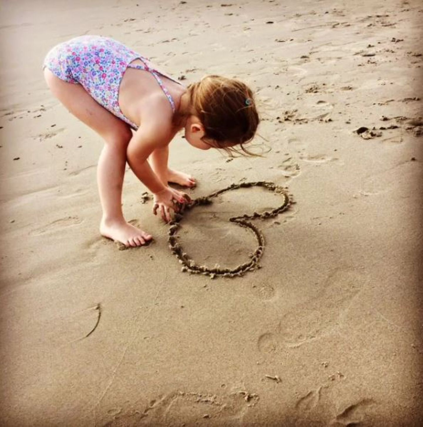 Dezember 2016   Theodora malt ein Herz in den Sandstrand und rührt damit ihre Mama. Ayda betitelt es mit Mamas Liebling.