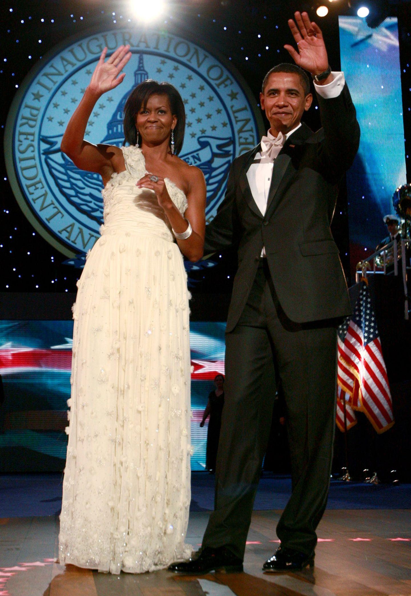 Abends beim Ball bezaubert die frischgebackene First Lady Michelle Obama im einem traumhaften weißen Ballkleid. Bei dem Designer ihres One-Shoulder-Kleides handelt es sich um Jason Wu, einbis dato noch eher unbekannten Designer. Natürlich konnte er sich nach diesem Auftritt kaum vor Aufträgen retten.