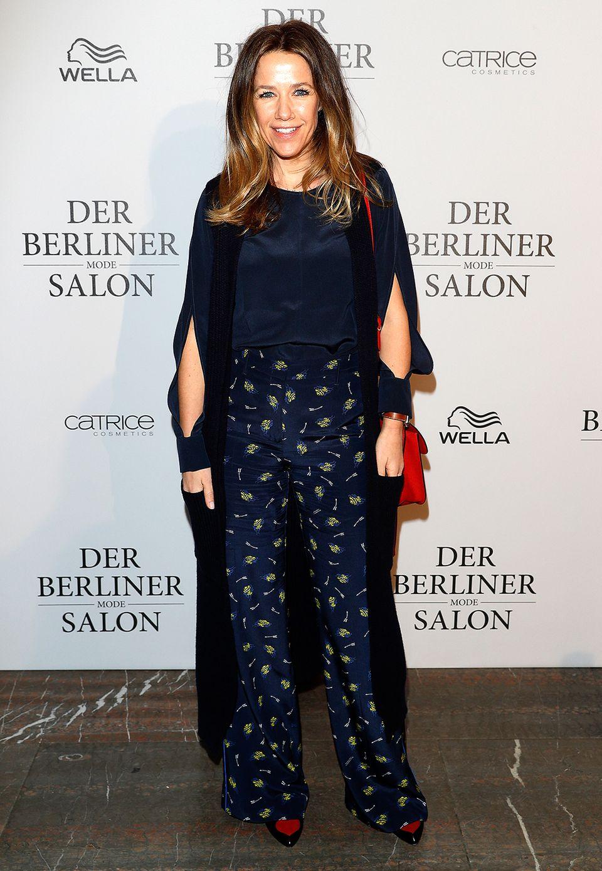 Alexandra Neldel kombiniert dunkelblau mit roten Accessoires.