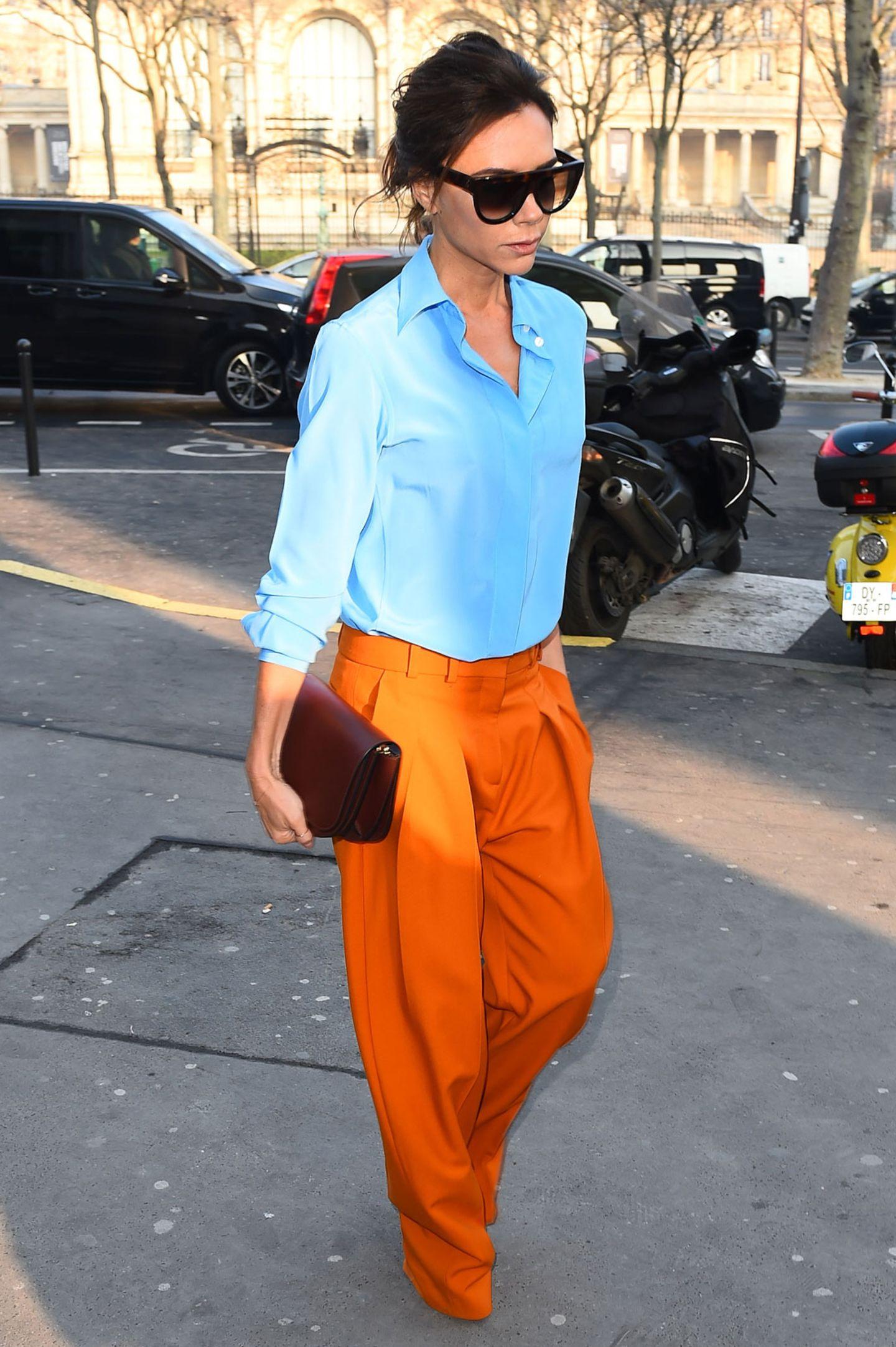 Wow, was für ein Auftritt! Victoria Beckham ist selbst wieder einmal ihr bestes Modell und begeistert im farbenfrohen Look, bestehend aus Oversized-Marlenehose und klassischer, blauer Bluse.