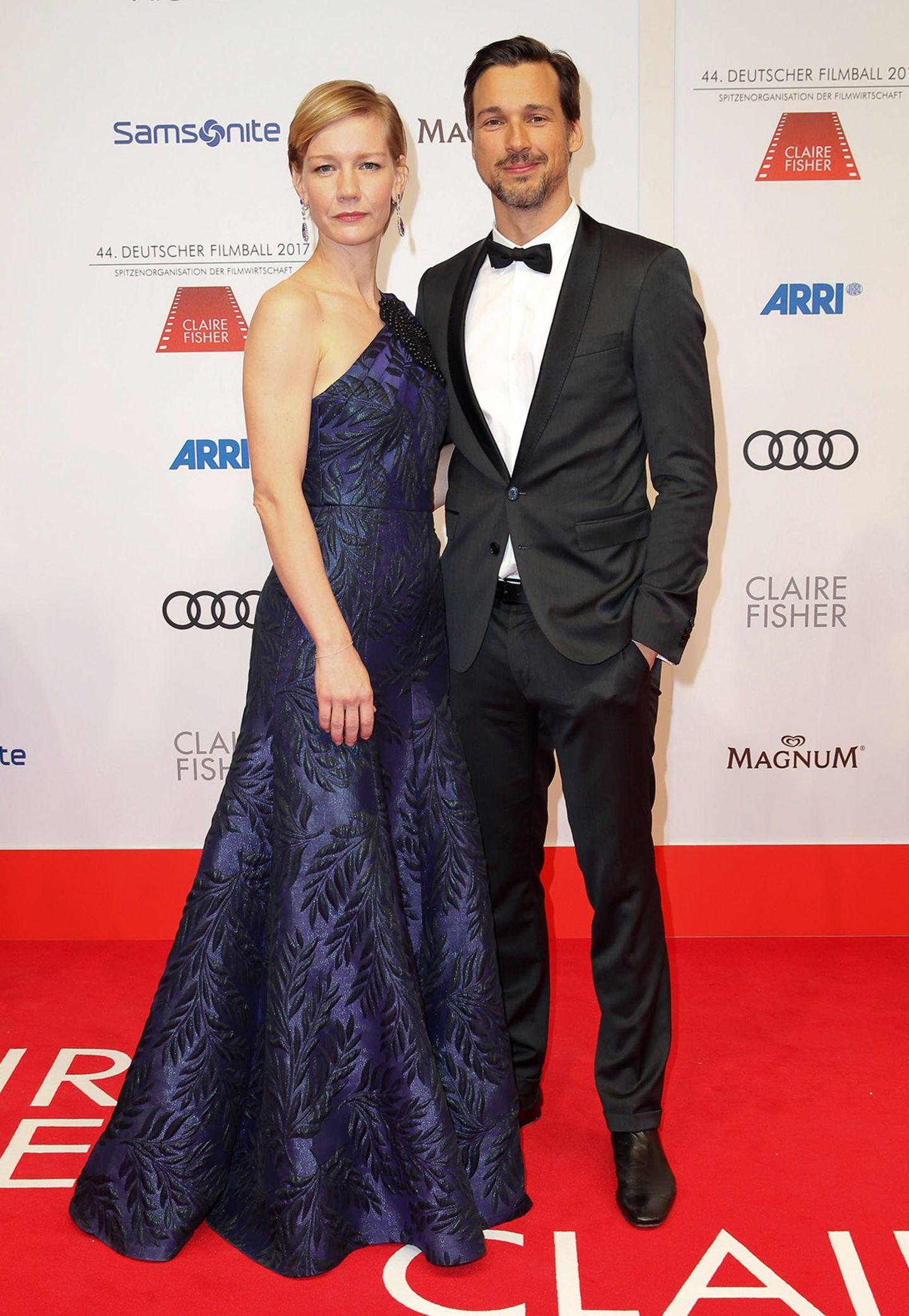 Sandra Hüller, hier mit Kollege Florian David Fitz, präsentiert sich mit glamouröser Blatt-Optik in dunklem Violett.