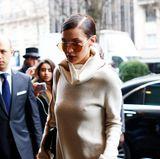 Pure Absicht oder reine Bequemlichkeit? Model Bella Hadid zeigt sich in Paris in einem kurzen Rollkragen-Kleid in Kombination mit Overknees. Auf einen BH verzichtet sie.