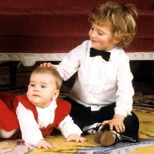 Weihnachten 1982 herrscht gute Laune. Prinz Carl Philip tätschelt Schwesterchen Madeleine des Kopf, Prinzessin Victoria lacht in die Kameras