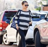 """Lässig bis zur Geburt: Die hochschwangere Natalie Portman trägt zum locker fallenden, gestreiften Sweater eine schmale Hose und schwarze Stiefeletten. Dazu kombiniert sie eine Statement-Tasche mit dem Aufdruck """"Make America Read Again"""". Ob sie wohl Bücher geshoppt hat?"""