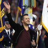 Countrysänger Luke Bryan winkt dem Publikum zu, bevor er die Nationalhymne zum Start des Super Bowls singt.