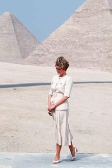 In einem sand-farbenen Ensemble mit Taillengürtel und großen goldenen Knöpfen posiert Prinzessin Diana vor den Pyramiden in Ägypten im Jahr 1992.