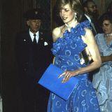 Prinzessin Dianas One-Shoulder-Kleid mit aufwendiger Rüschenstruktur lenkt zum Glück von ihrem etwas müden Blick ab und bildet zusammen mit der gold-farbenen Clutch ein tolles Abendoutfit für ein Bankett in London im Jahr 1982. Ihre schlanke Silhuette, die von diesem Kleid extra betont wurde, sorgte für Gerüchte um eine angebliche Anorexie, die Prinzessin Diana dann Jahre später bestätigte.