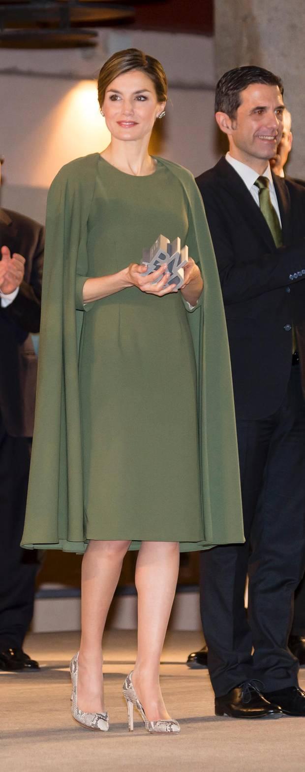 Bei einer Preisverleihung in Madrid trägt Königin Letizia ein tolles khaki-farbenes Cape-Kleid und als Hingucker Pumps mit Schlangenmuster.