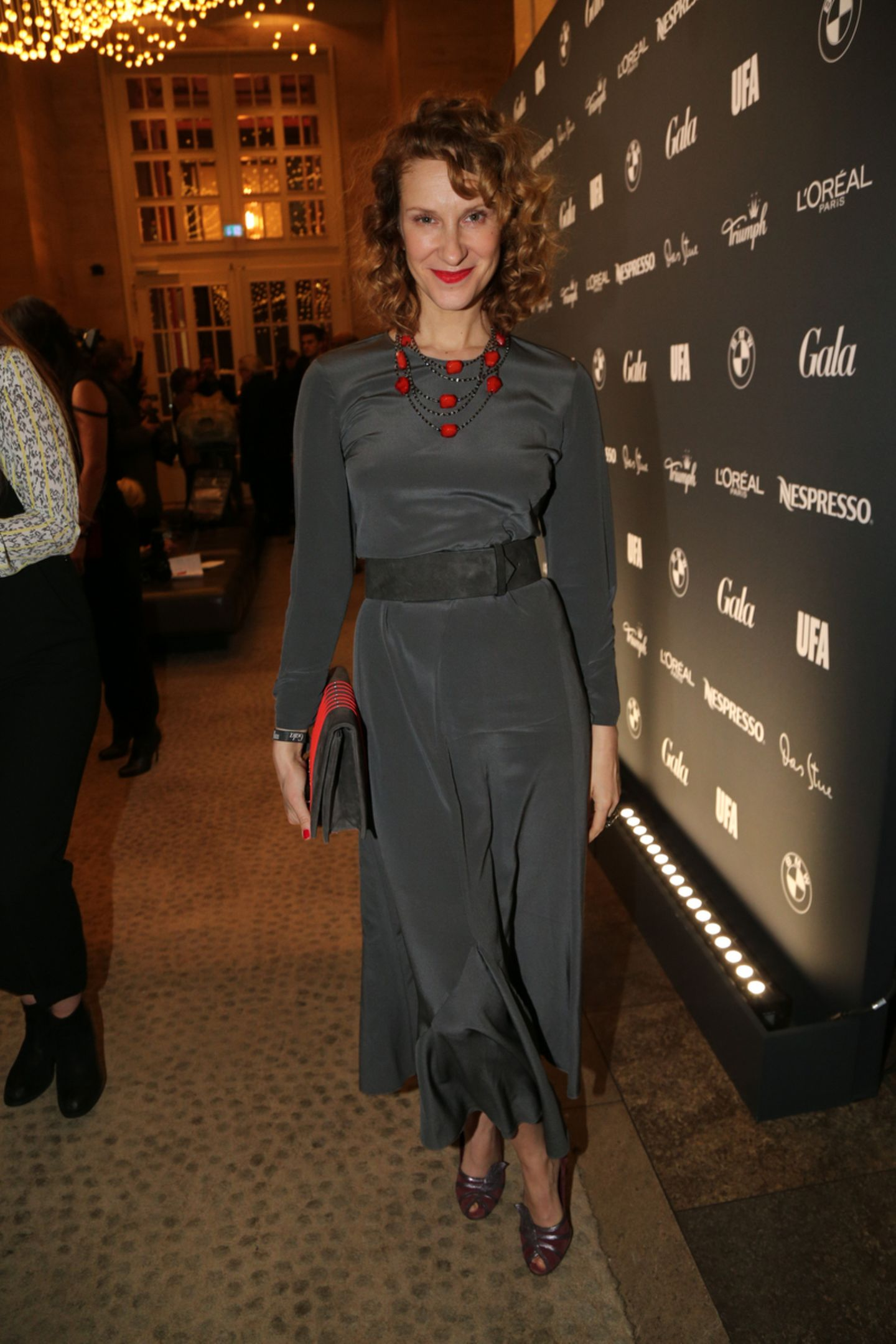 Schauspielerin Chiara Schoras sieht in ihrem grauen Abendkleid mit roten Akzenten einfach umwerfend aus.
