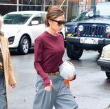 Aktuell sieht man Fashionista Victoria Beckham fast ausschließlich in Oversize-Marlenehosen durch die Straßen flanieren. Hier in einem braunen Ledergürtel zum grauen Modell kombiniert.