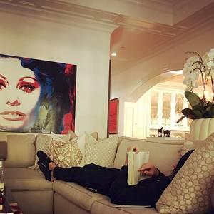Sofia Vergara wundert sich, wie ihr Göttergatte Joe Manganiello mit Kapuze über den Kopf gezogen, lesen kann. Eigentlich möchte sie nur seine Aufmerksamkeit. Aber gegen den Sonntagschmöker auf der gemütlichen Couch kommt sie nicht an. Auffallend ist, das übergroße Porträt der Filmlegende Sophia Loren. Es gibt dem Wohnraum den nötigen Farbakzent und Glamour.