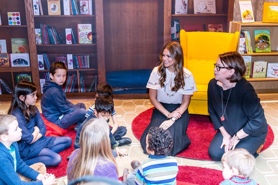 Ein bisschen skeptisch schauen die kleinen Engländer schon, aber Prinzessin Madeleine von Schweden erweist sich als bestens aufgelegt, als sie zu ihnen in die Leseecke kommt.