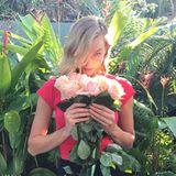 Model Karlie Kloss schnuppert an einem Strauß Rosen.