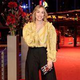 """Nina Hoss zeigt sich mit extravaganter Seidenbluse und Marlene-Hose auf dem roten Premierenteppich von """"Return to Montauk"""" modisch wagemutig."""