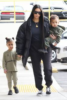 In einem ungewohnt legeren Outfit verlässt Kim Kardashian mit ihren Kindern ein Restaurant in Los Angeles: Sie trägt eine dicke Daunenjacke, ein schlichtes Oberteil und eine weite Sweatpants mit Vans. Auf dem Arm trägt sie keine teure Designertasche, sondern Söhnchen Saint. Töchterchen North scheint das Essen nicht geschmeckt zu haben, oder gefällt ihr etwa Mamas Look nicht?Quengelig läuft sie an Mamas Hand nebenher. Die Looks der beiden Kleinen sind ebenfalls ungezwungen, sportlich und perfekt aufeinander abgestimmt. Beide tragen Outfits aus der neuesten Kollektion von Papa Kanye West.