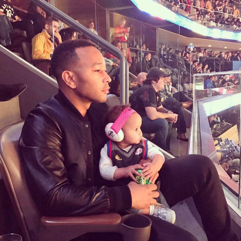 John Legend bringt seine kleine Luna mit zum Basketball. Damit es der Süßen nicht zu laut wird, hat er ihr Lärmschutz-Kopfhörer aufgesetzt.