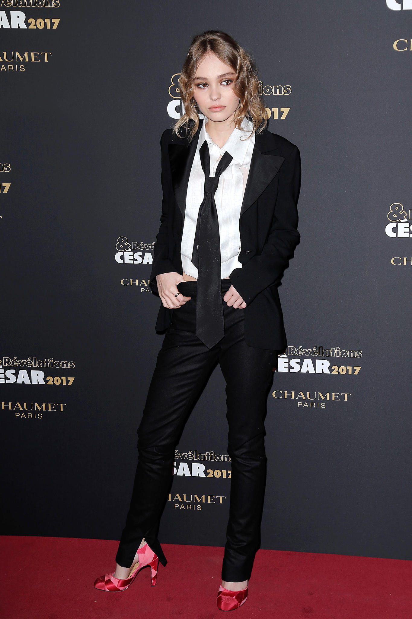 Lily-Rose Depp trägt zum schwarzen Anzug und der casual gebundenen Krawatte sehr feminine Schuhe