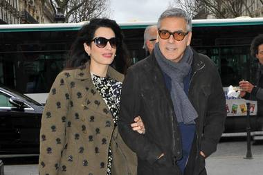 Verliebt in Paris zeigt sich Amal Clooney in einem blumigen Kleid mit coolem khakifarbenen Mantel.