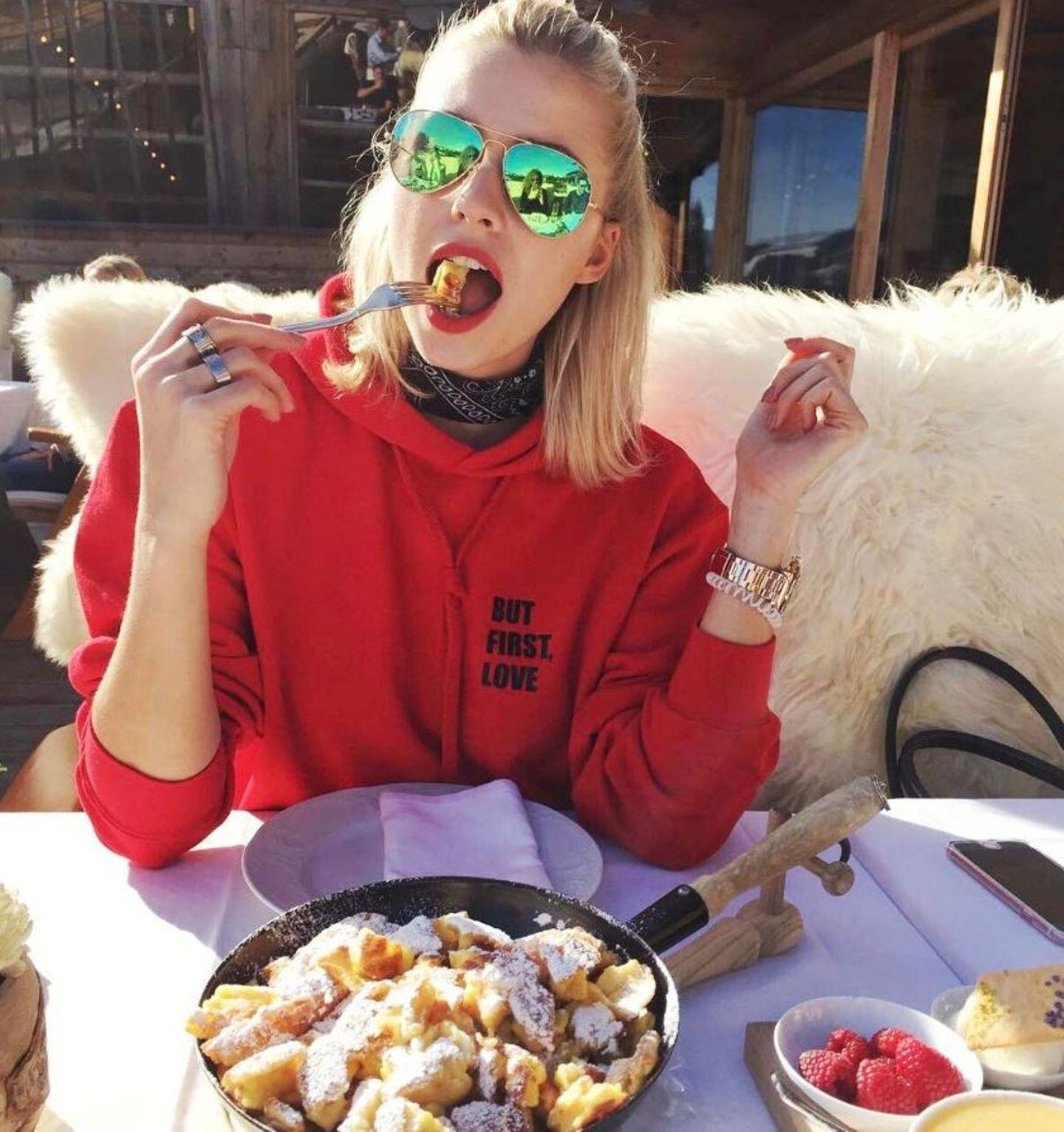 """Zum neidisch werden: Topmodel Lena Gercke genießt eine Portion Kaiserschmarrn bei strahlendem Sonnenschein in Kitzbühel. Noch schöner ist allerdings das Statement auf Lenas rotem Sweatshirt: """"BUT FIRST, LOVE"""""""