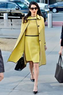Ein echter Sonnenschein ist Amal Clooney in diesem Ensemble von Bottega Veneta. Die Kombination aus Kleid und Mantel in gelb-schwarz steht ihr ganz ausgezeichnet. Doch alle fragen sich: Wo ist denn ihr Babybauch?