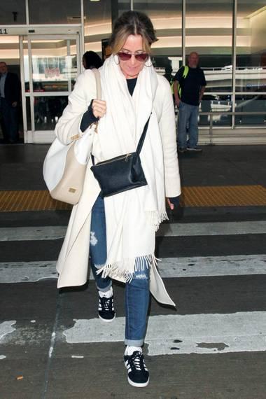 """Auch Felicity Huffman hat die """"Gazellen"""" für sich wiederentdeckt. Als hätte sie sich mit Emma Roberts abgesprochen, trägt auch sie einen hellen Mantel zu den Sportschuhen."""