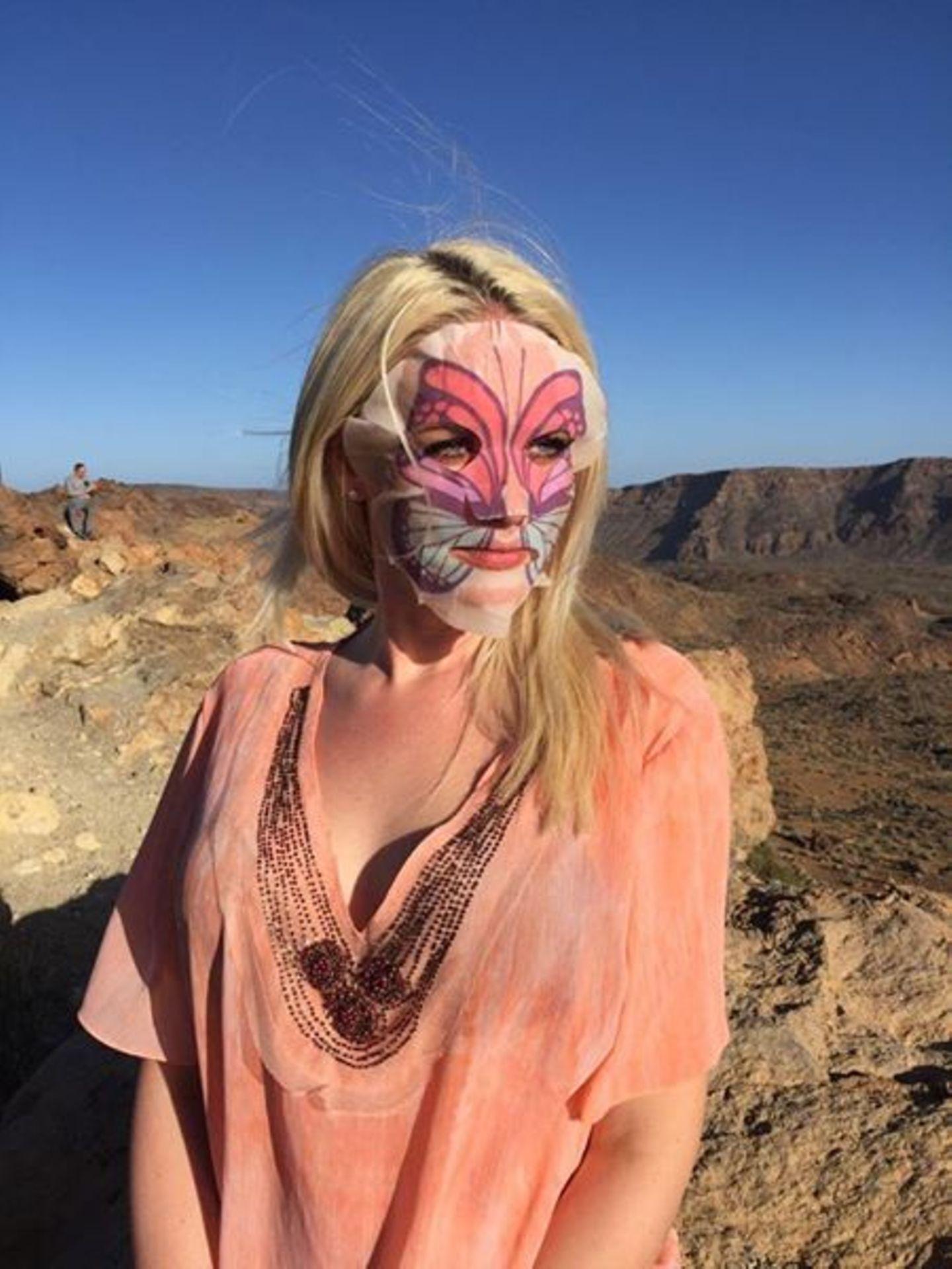 Wer versteckt sich denn hier hinter einer wohltuenden Schmetterlinksmaske? Es ist Ex-GNTM-Teilnehmerin Sarah Knappik, die ihrer Haut im Urlaub etwas Gutes tut.